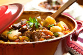 Traditional goulash or beef stew, in red crock pot, ready to serve.  Shallow DOF.  More beef images: