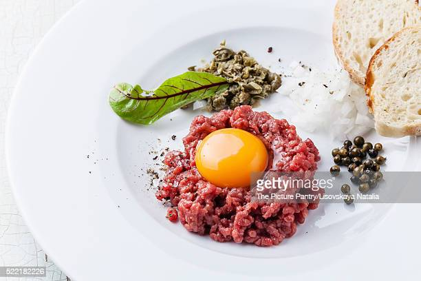 Beef tartare with capers and bread on white plate