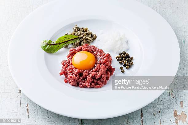 Beef tartare with capers and onion on white plate