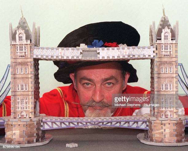 Beefeater Basil Holland peers through a three dimensional jigsaw model of the Tower Bridge The bridge is one of the PUZZ 3D range of scale models of...