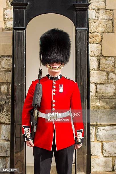 A beefeater palace guard guardsman is wearing a traditional bearskin hat at the Tower of London on April 15 2012 in London England United Kingdom
