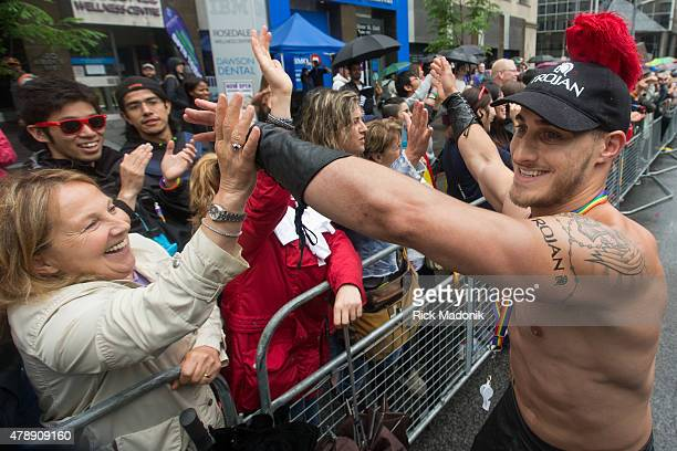 TORONTO JUNE 28 2015 A beefy man works the crowd along Bloor Street East Toronto Pride 2015 took over the downtown core as the annual Pride Parade...