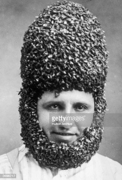 Beekeeper Frank Bornhofer wearing a helmet and beard composed of bees in order to prove they do not sting