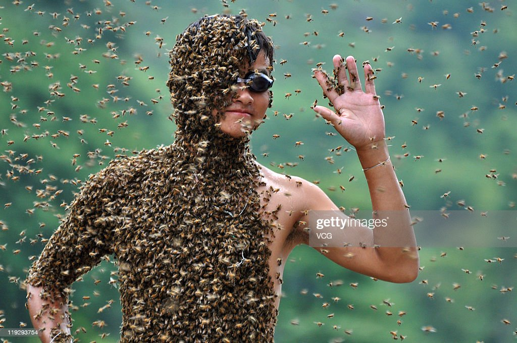 Beekeeper Lu Kongjiang waves as he competes in a 'bee bearding' contest on July 16, 2011 in Shaoyang, Hunan Province of China. Wang Dalin won the contest after attracting 26.86kg of bees onto his body, covered only by a pair of shorts and swimming goggles.