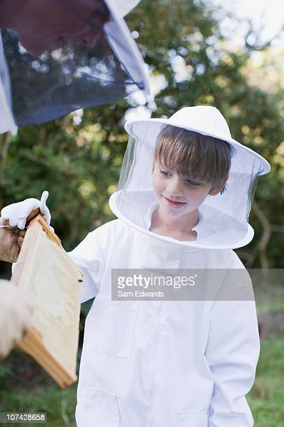 Beekeeper showing honeycomb to boy