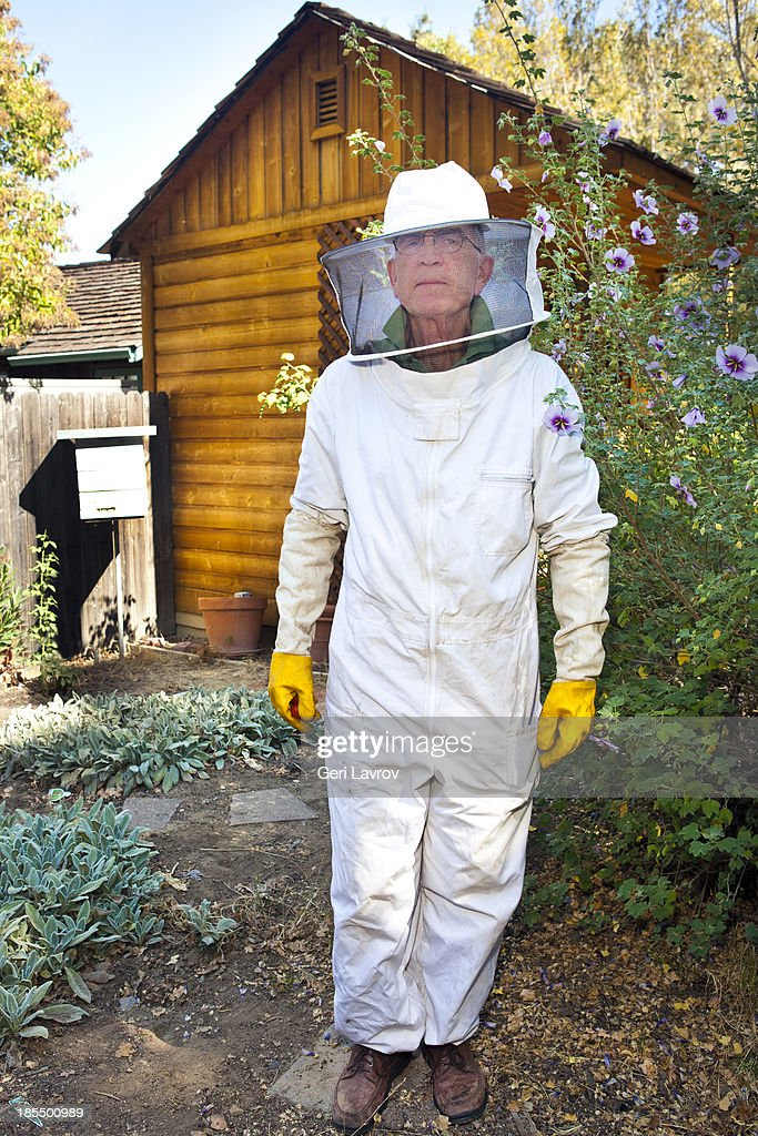 Beekeeper standing by his bee hive