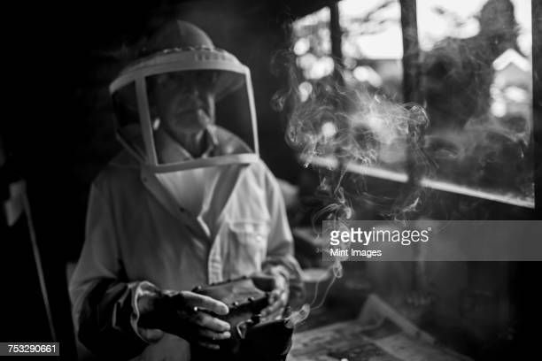 A beekeeper wearing protective clothing and holding a smoker for calming honeybees.
