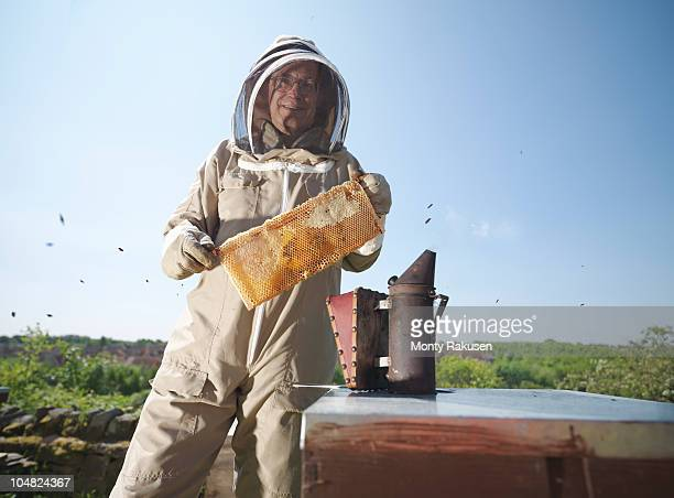 Beekeeper with honey comb and smoker