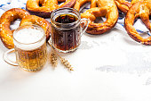 Light and dark beer and pretzels on white background. Oktoberfest party