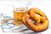 Light beer in a glass and traditional bavarian pretzel. Oktoberfest background