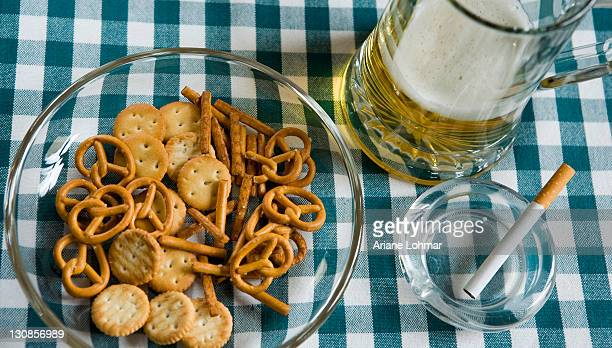 Beer, beer glass, cigarette, ashtray, savoury biscuits