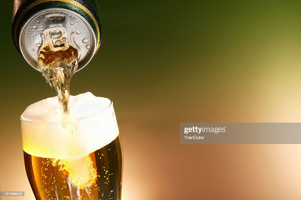 Beer being poured from a can into a glass : Stock Photo