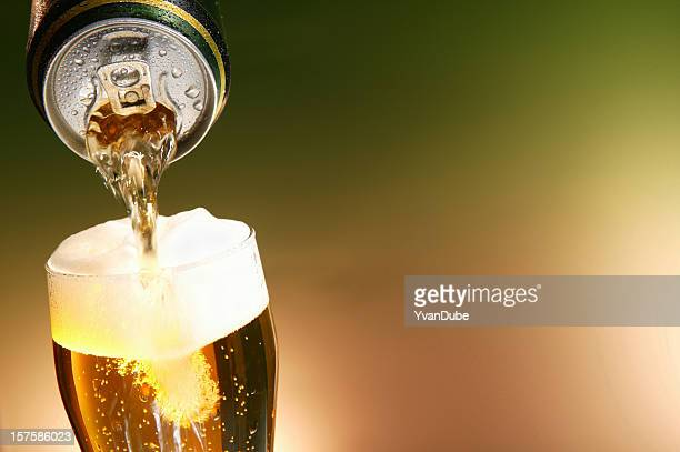 Beer being poured from a can into a glass