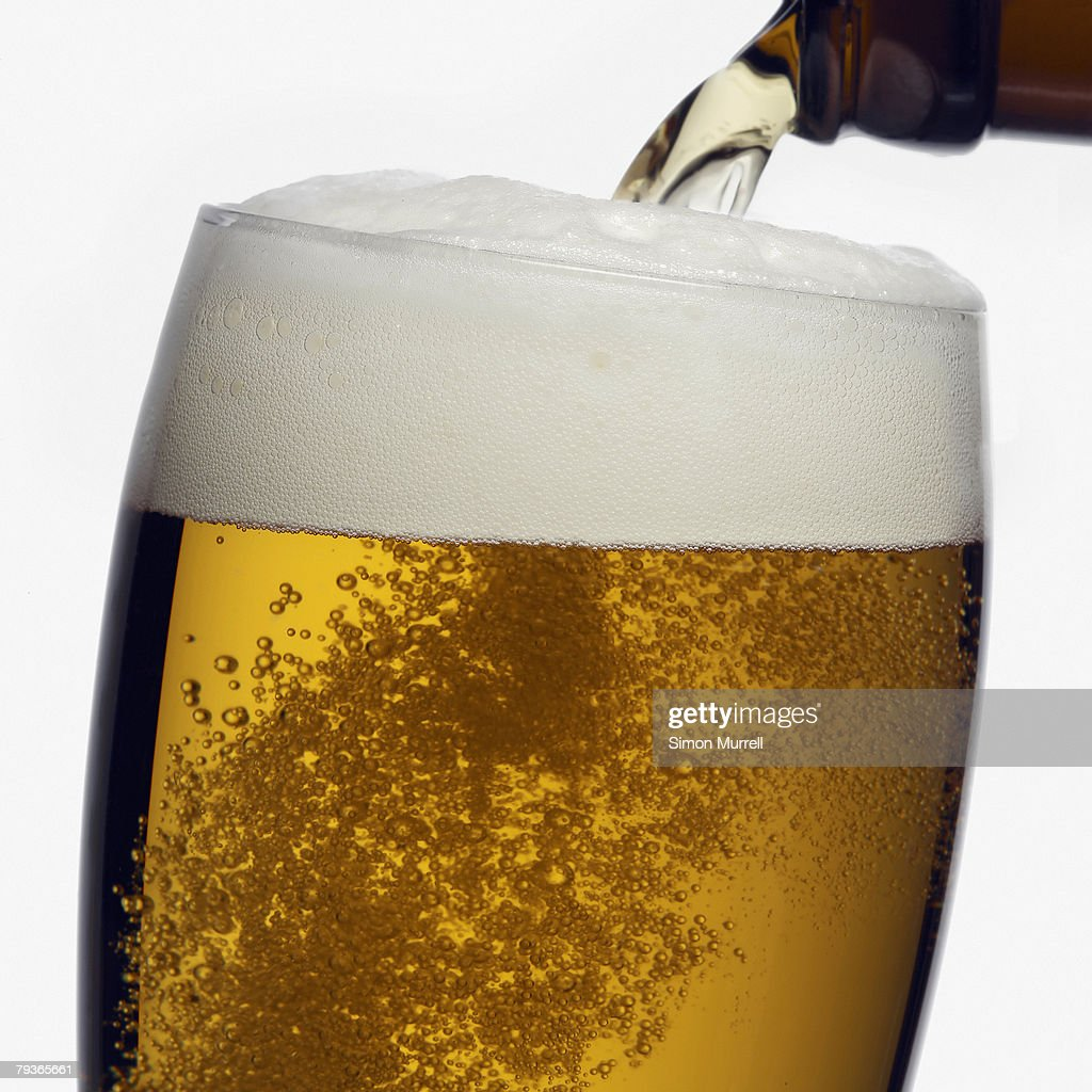 Beer being poured into glass : Stock Photo