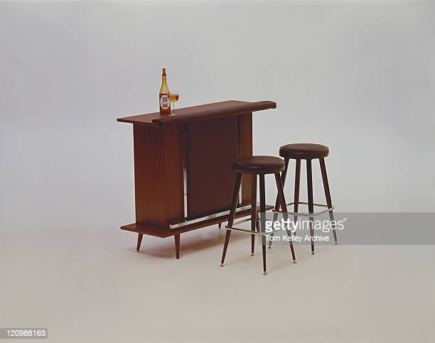 Beer bottle and glasses on wooden table beside wooden stools