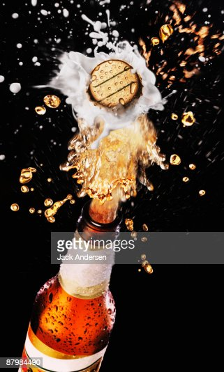 Beer bottle cap bursting with splashing beer