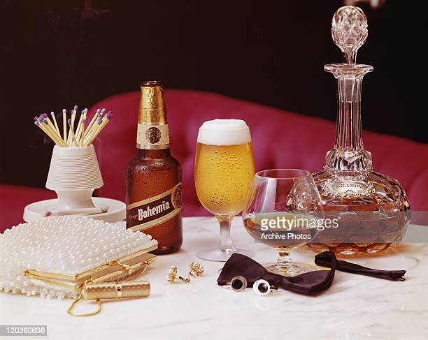 Beer bottle, carafe, purse and ashtray on table