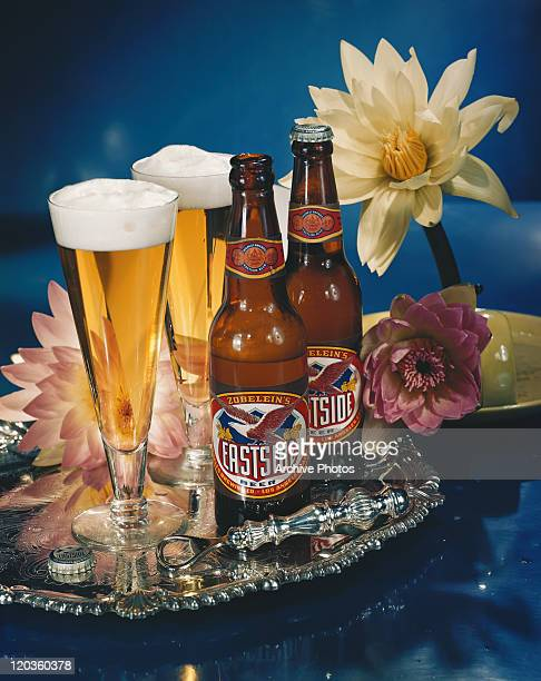 Beer bottle with beer glasses and water lilies, close-up