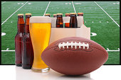 Six pack of beer and frothy glass with an American Football in front of a big screen television. Great for Super Bowl themed projects.