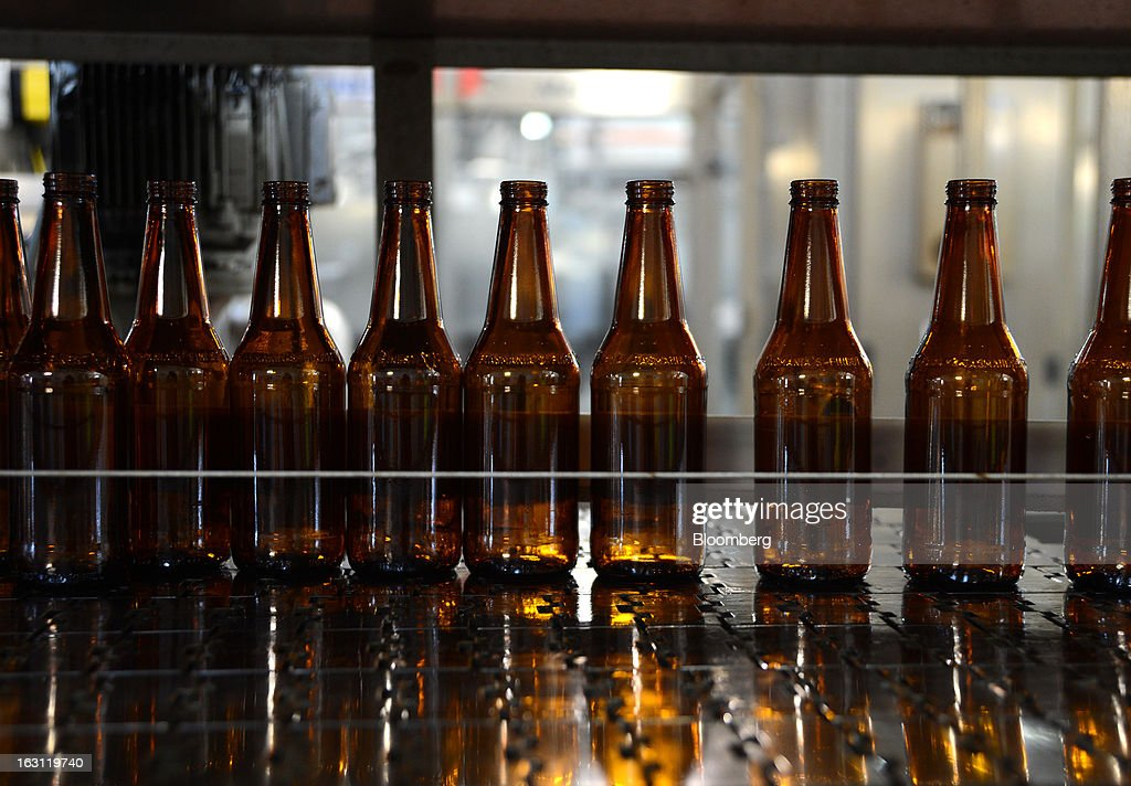 Beer bottles line a conveyor belt as they stand ready for bottling at the Boag's brewery, operated by Kirin Holdings Co.'s Lion unit, in Launceston, Tasmania, Australia, on Monday, Feb. 25, 2013. Australia's Bureau of Statistics is scheduled to release fourth-quarter gross domestic product figures on March 6. Photographer: Carla Gottgens/Bloomberg via Getty Images