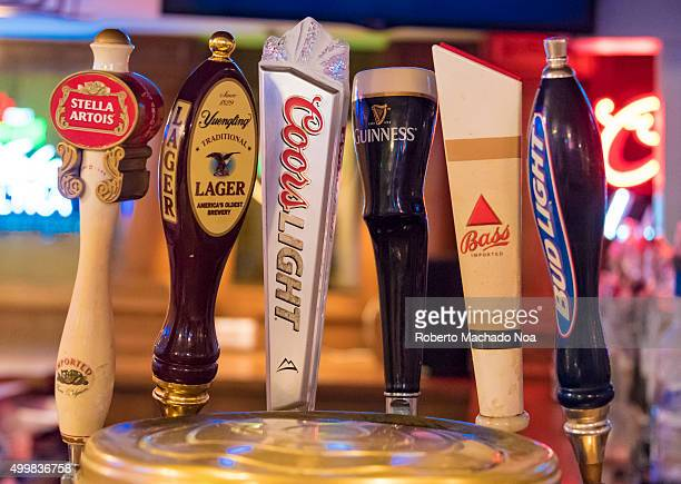Beer dispensers or tap handles with brand names on them inside a bar in New York City USA