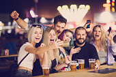 Group of friends drinking beer and taking selfie at beer festival