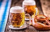 Beer. Oktoberfest.Two cold beers and pretzel. Draft beer. But draft. Golden beer. Golden however. Two gold beer with froth on top. Cold draft beer in glass jars in a hotel pub or restaurant. Still lif