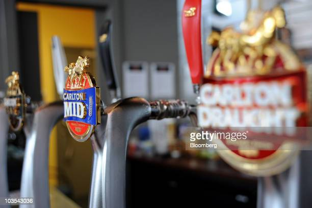 Beer taps are marked with a Carlton Draught Mid and Dark logos at Foster's Group Ltd's Carlton United Breweries visitors centre bar in Abbottsford...