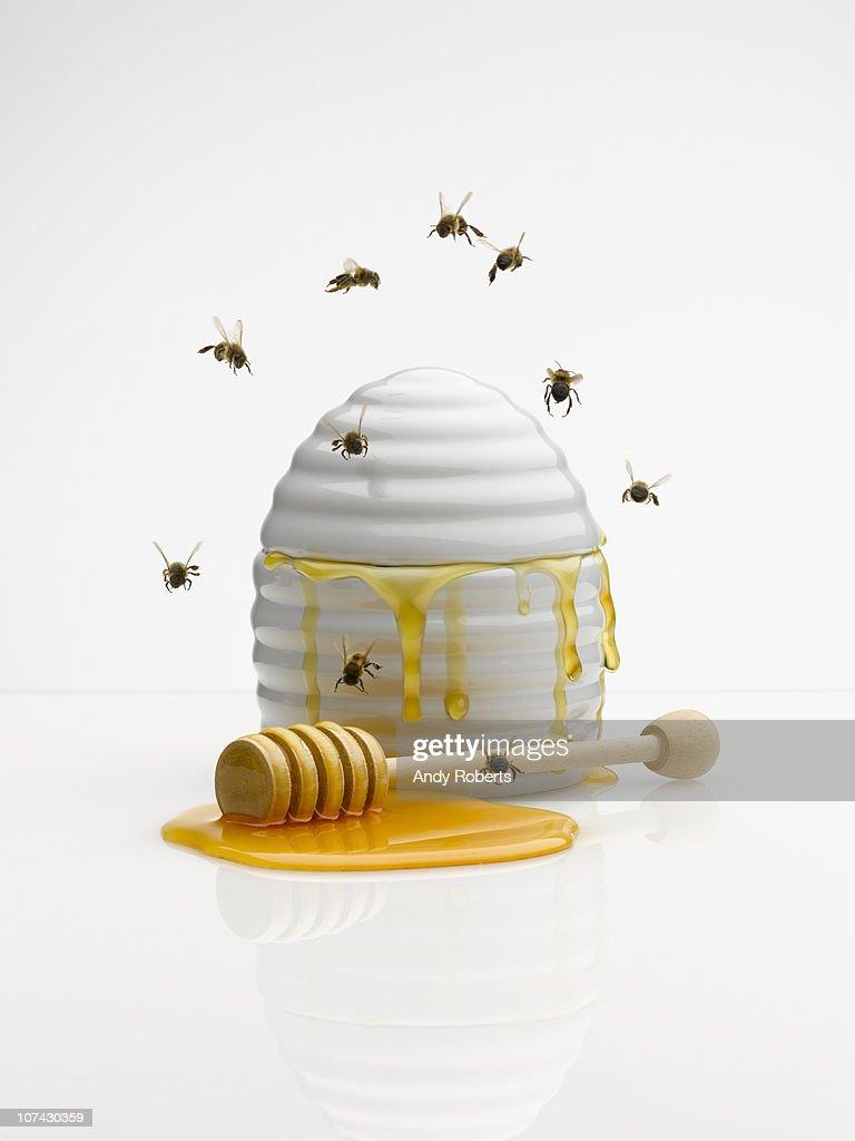 Bees flying around honey jar : Stock Photo