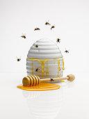 Bees flying around honey jar