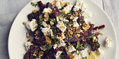 Beetroot salad with cottage cheese and walnuts. European cuisine. Organic food. Vegetarian appetizer. Simple side dish. Wide photo. Close up.