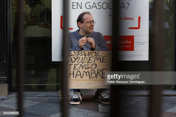 A beggar asks for alms in the street with a placard reading 'I am Spanish Help me I am hungry' on October 11 2013 in Madrid Spain Madrid Mayor Ana...