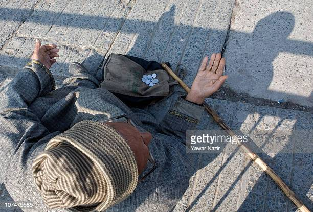 A beggar begs on a road on December 9 2010 in Srinagar the summer capital of Indian administered Kashmir India Kashmir has witnessed an unprecedented...