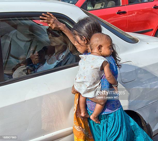 CONTENT] MAHIM MUMBAI INDIA beggar child holds baby begging at the corner light Rich Indian seen in the car