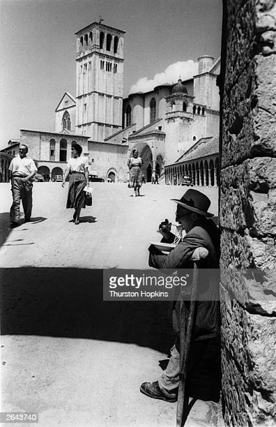 A beggar eating spaghetti on a street corner in Assisi Original Publication Picture Post 5409 Assisi pub 1951