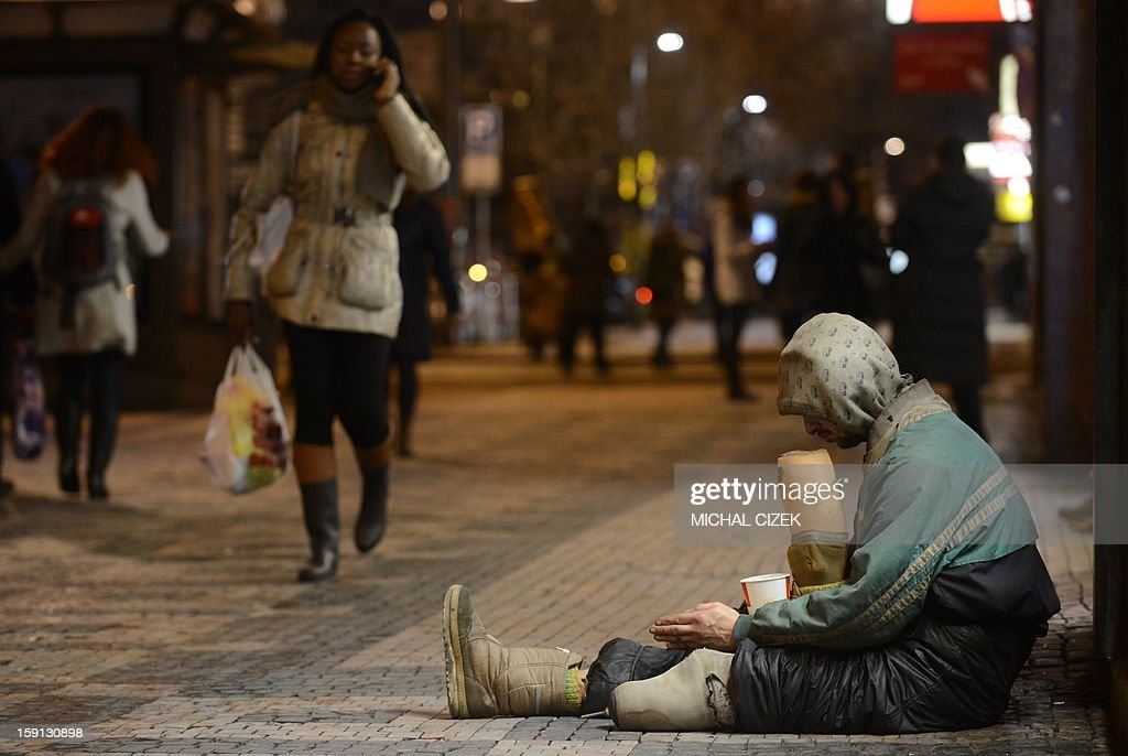 A beggar holding his foot prostheses waits for alms on January 8, 2013 in Prague.