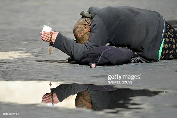 A beggar lies on the ground asking for some money while holding a rosary in a street of Rome on March 24 2014 AFP PHOTO / GABRIEL BOUYS