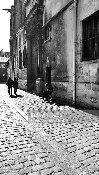 Beggar Playing Guitar On Street Against Building