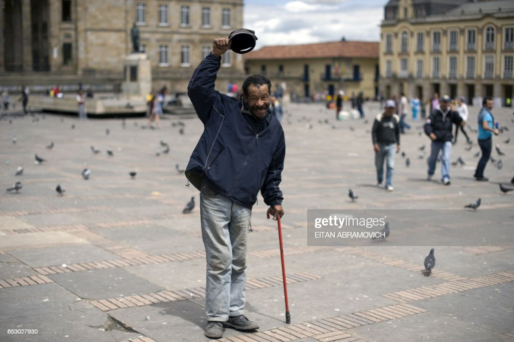 A beggar poses for a picture at Bolivar Square in downtown Bogota, Colombia, on June 19, 2010. Nearly 30 million voters head to the polls Sunday to choose a successor to President Alvaro Uribe. The run-off pits frontrunner ex-defense minister Juan Manuel Santos and former two-time Bogota mayor Antanas Mockus. The two came out ahead in the first round of votes on May 30, but fell short of the 50 percent required for an outright win.AFP PHOTO/Eitan Abramovich /