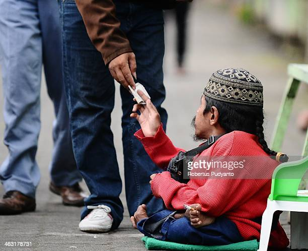 A beggar receives money from pilgrims near the ancestor cemetery at Mount Kawi on January 17 2014 in Malang Indonesia Mount Kawi is one of the most...