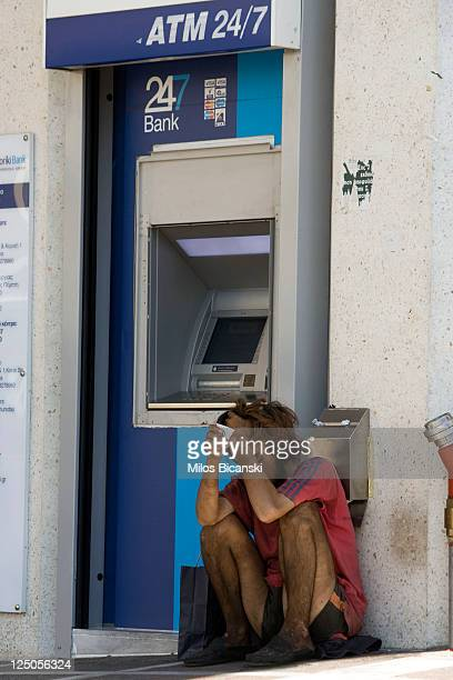 A beggar sits in front of Emboriki Bank in downtown Athens on September 15 2011 in Greece As Greece's position in the Eurozone remains uncertain a...