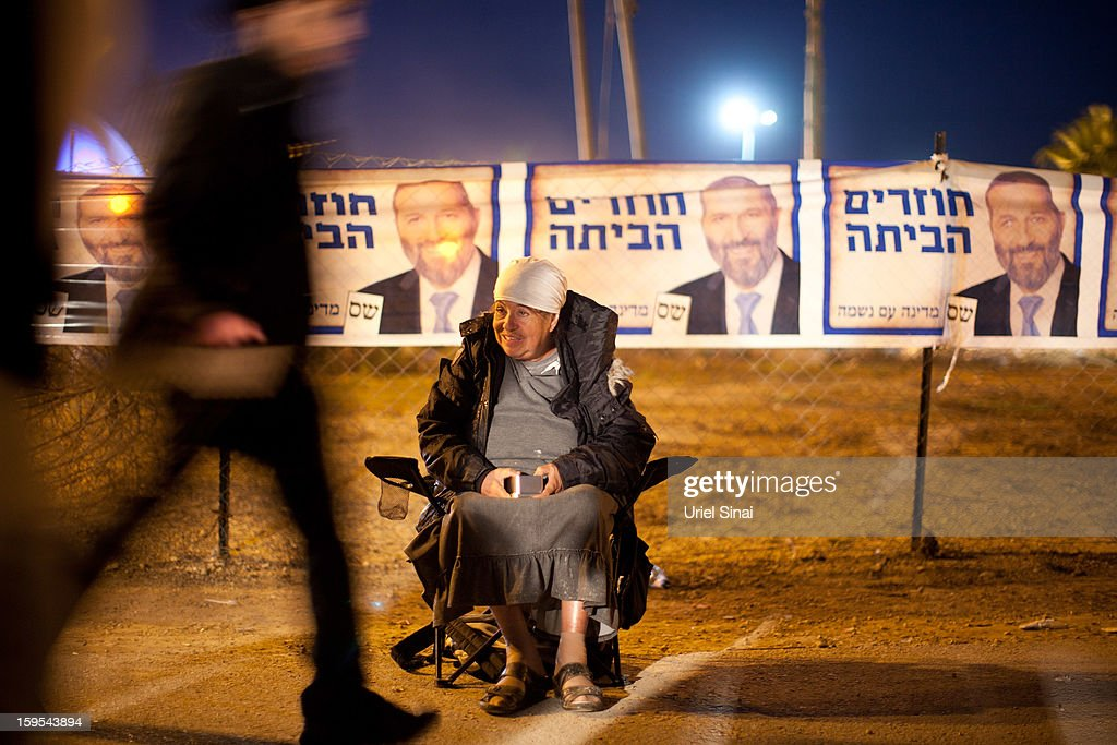 A beggar sits in front of posters of the ultra-Orthodox Shas party ahead of the upcoming Israeli elections during the annual pilgrimage to the grave of Rabbi Baba Sali in the southern Israeli town of Netivot on January 15, 2013 in the southern Israeli town of Netivot, Israel. Thousands of Jews, mainly of Moroccan origin, gathered to pray and hold festivities at the tomb of the respected rabbi who was known as a miracle maker by religious Jews.