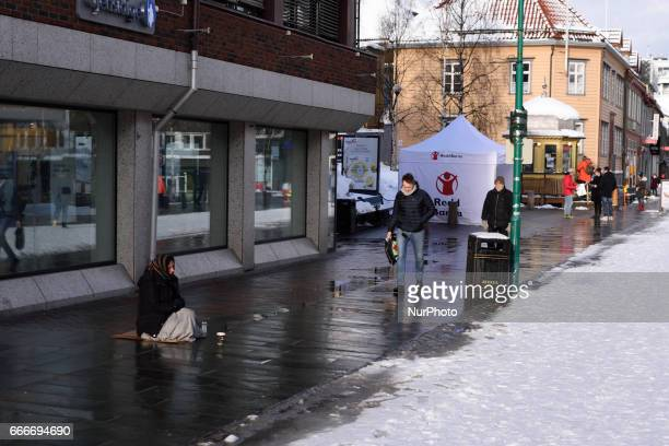 A begger sists on the wet pavement in a snowcovered street in the city of Tromso Northern Norway on March 10 2017 Troms is located 350 kilometres...