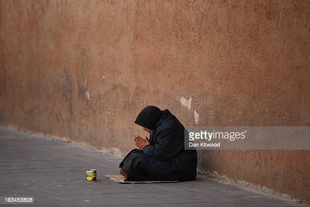 A begger sits by the side of the road near the Colosseum on March 10 2013 in Rome Italy Cardinals are set to enter the conclave to elect a successor...