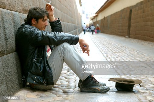 Begging man sitting near Inca wall in Cuzco, Peru