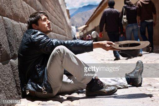 Begging man sitting near Inca wall