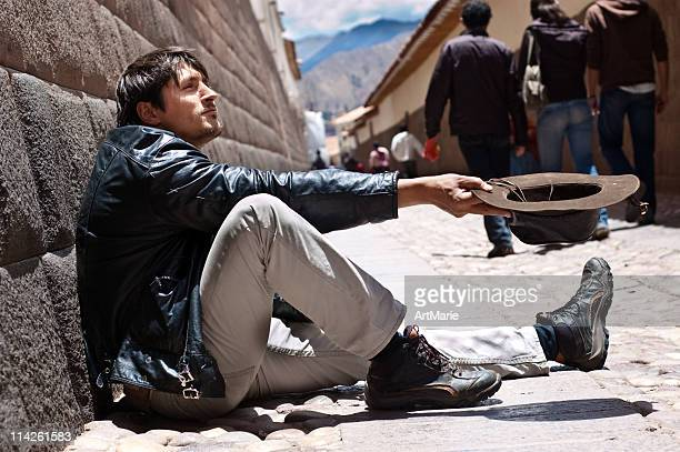 Begging man sitting near Inca wall