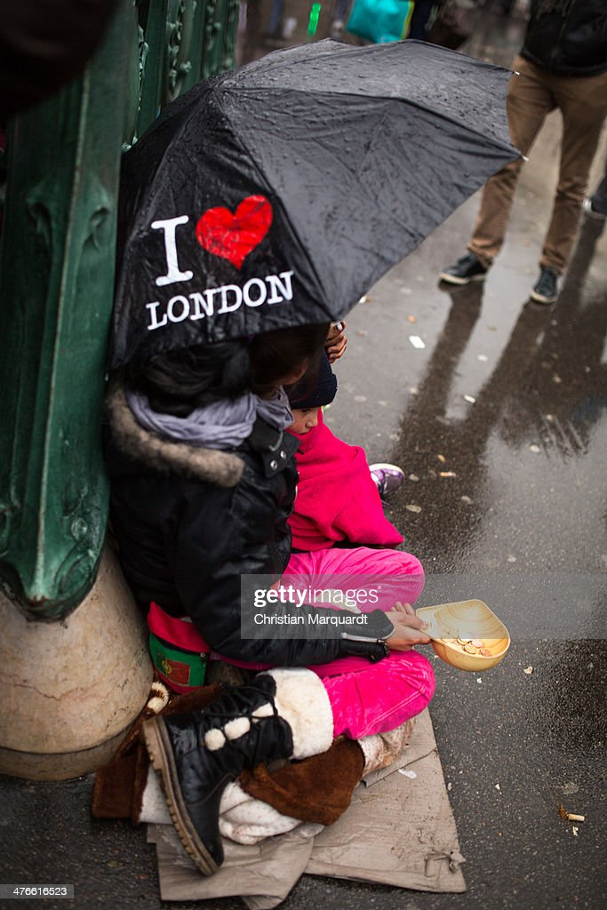 A begging woman in the northern Parisian district Montmatre holds a umbrella with the inscription 'I Love London' during a rainy day on March 1, 2014 in Paris, France.