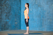 Side view portrait of beautiful young woman dressed in bright sportswear enjoying yoga indoors. Yogi girl working out in grunge interior with textured blue wall. Standing in tadasana. Full length