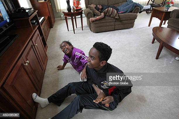 Behaylu Barry tickles the feet of his sister Eden 9 He is a 13yearold boy adopted from Ethiopia who has a rare blood disorder His parents arranged...